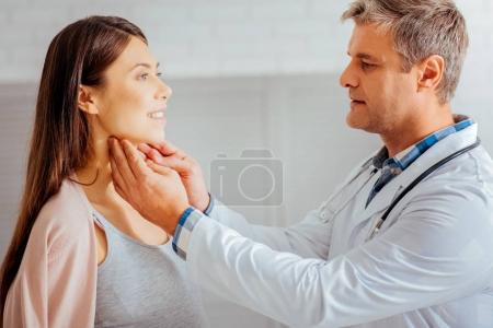Male doctor checking lymph nodes of pregnant woman