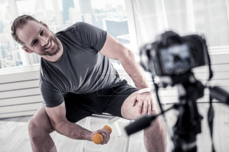 Joyful male blogger keeping biceps in shape