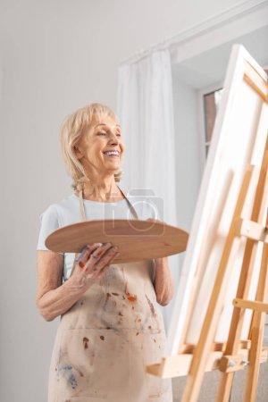 Glad mature woman enjoying her masterpiece