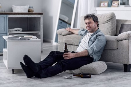 Smiling untidy man drinking alcohol and watching TV at home