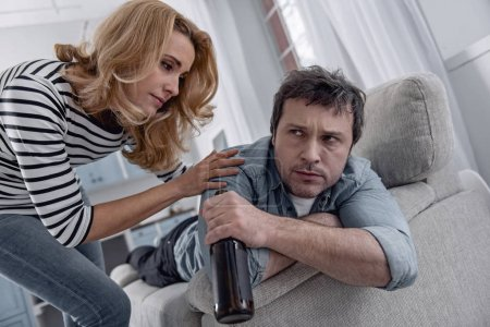 Alcoholic man frowning while his loving wife kindly looking at him
