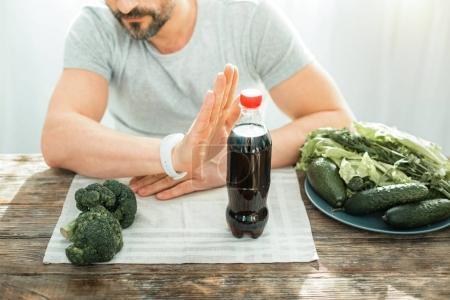 Photo pour Mauvaise idée. Homme décisif concentré inébranlable refusant de boire du cola gesticulant et assis à la table. - image libre de droit