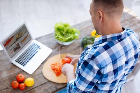 Young attentive man preparing healthy dish