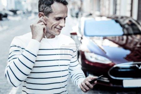 Joyful positive man wearing headphones