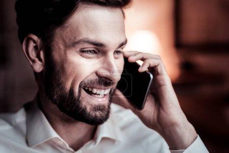 Photo pour Mon cher ami. Joyeux intéressé homme inébranlable tenant son téléphone portable près de la tête avoir la conversation et rire . - image libre de droit