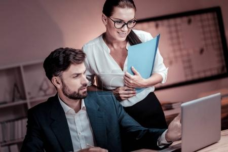 Photo for Good results. Satisfied pretty bespectacled woman standing near her colleague looking at the laptop and holding the folder. - Royalty Free Image