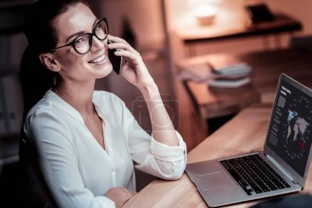 Photo for Important call. Occupied pleasant bespectacled woman sitting in the office by her desktop having phone conversation and using the laptop. - Royalty Free Image