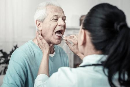 Gray aged man having examination and sitting opposite the nurse.