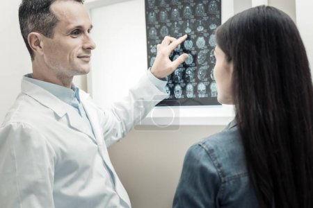 Photo for Professional interaction. Cheerful handsome positive doctor smiling and looking at his patient while pointing at the X ray scan - Royalty Free Image