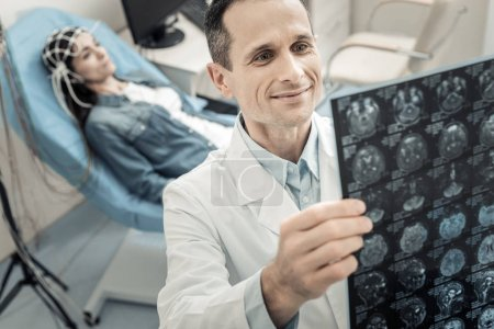 Positive delighted doctor looking at the X ray photo