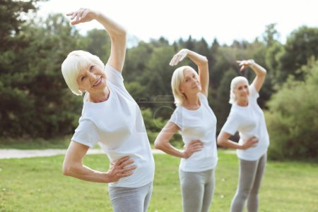 Photo for Staying fit. Happy positive aged woman smiling and doing the bending exercise while enjoying it - Royalty Free Image