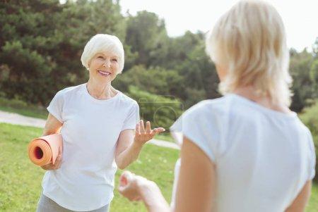 Photo pour Jolie communication. Heureuse enchantée femme âgée souriante et parlant à son ami tout en tenant un tapis de yoga - image libre de droit
