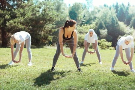 Joyful active women repeating after trainer