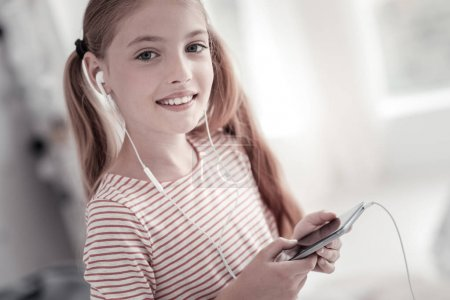Gleeful cute girl listening to music
