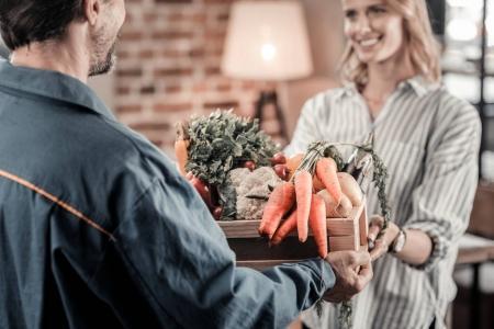 Photo pour Légumes frais. Concentration sélective d'une boîte avec des légumes étant entre les mains d'un livreur professionnel - image libre de droit