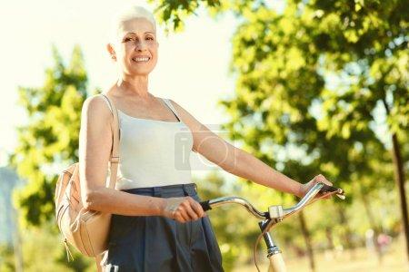 Positive elderly woman holding her bike