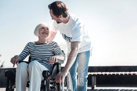 Nice pleasant man helping an elderly woman