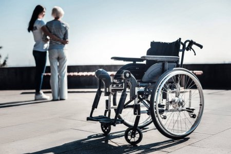 Photo for For disabled people. Selective focus of a wheelchair standing on the ground with nice positive people walking in the background - Royalty Free Image
