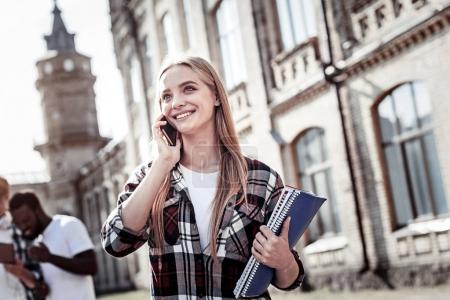 Nice positive woman putting smartphone to her ear