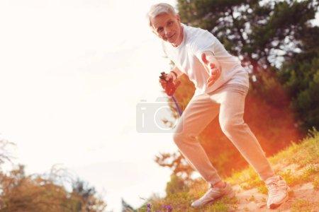 Full length of elderly man putting his hand forward