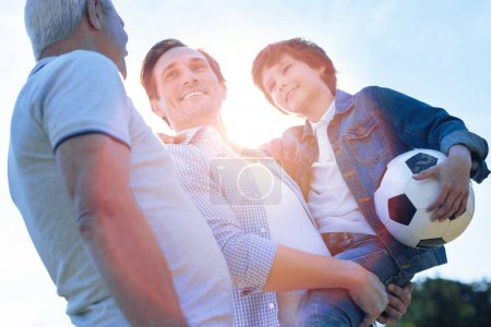 Cheerful family discussing soccer after playing outdoors