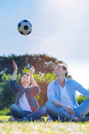 Photo pour On s'amuse tellement ensemble. Père et fils excités assis dans l'herbe et souriant largement tout en lançant une balle et en se réchauffant avant un jeu de famille . - image libre de droit
