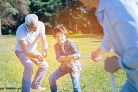 Adorable grandfather cheering for grandson competing with father