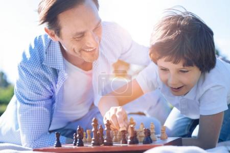 Proud father watching son playing chess