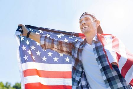 True patriot smiling cheerfully while holding american flag