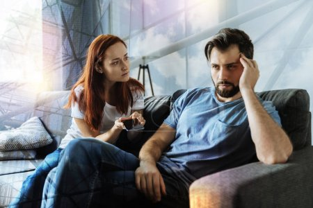 Young irritated man turning from his girlfriend and not looking at her