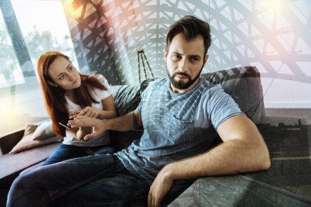 Besorgte Frau hält Smartphone in der Hand, während ihr Freund sich weigert, es zu sehen