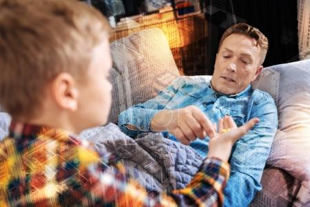 Careful man resting on the sofa and taking a little pill from his son