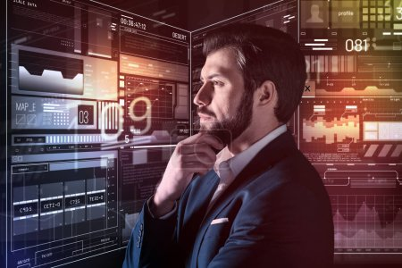 Serious young person touching his beard and looking thoughtful