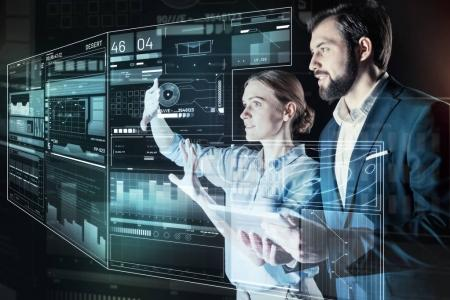 Young woman touching the screen while her colleague looking at it
