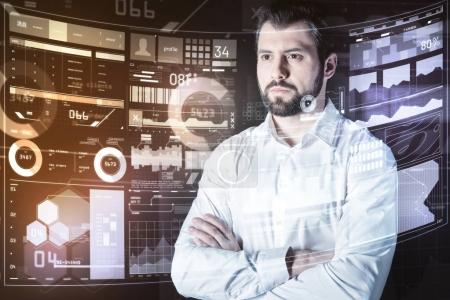 Confident programmer standing with his arms crossed and thinking