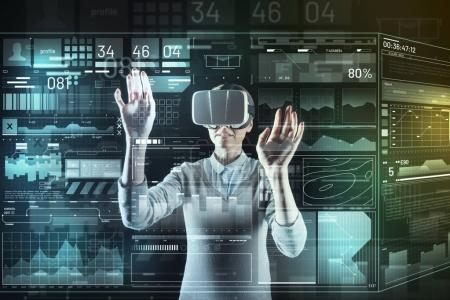 Photo for Unusual device. Progressive smart experienced programmer feeling interested while standing with her hands up and carefully working in modern virtual reality glasses - Royalty Free Image