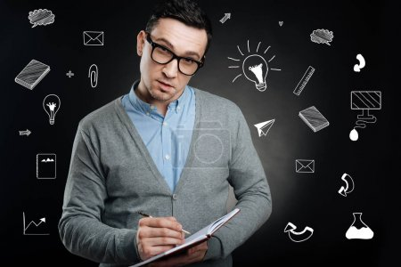 Strict teacher leaning his head while standing with a notebook