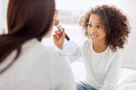 Content girl putting on make-up on her moms face