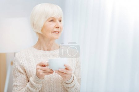 Pleasant elderly woman holding a cup and looking into the distance