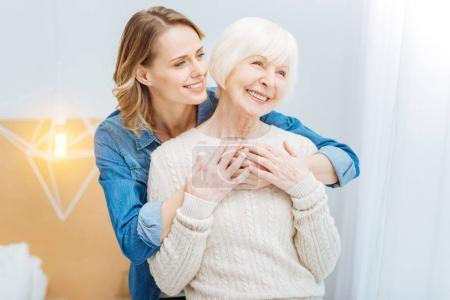 Kind attentive woman hugging her grandmother and smiling cheerfully