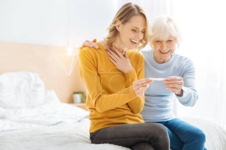 Excited emotional relatives happy while seeing the results of pregnancy test