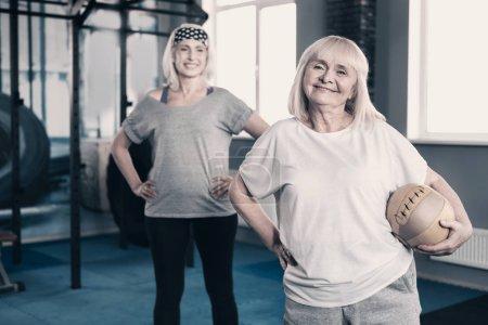 Photo pour Jeunes âmes. Chambre de charme optimiste senior Dames debout dans la salle de gym et posant pour la caméra alors que l'un d'eux tenant une boule de médecine - image libre de droit