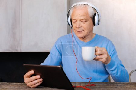 Pleasant elderly man relaxing at home
