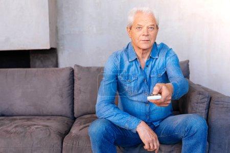 Nice elderly man holding a remote control