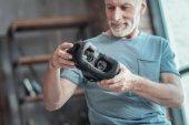 Interested senior man standing and holding the VR glasses.