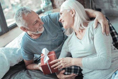 Photo pour Je t'aime tellement. Charmant couple mignon aîné couché sur le lit ensemble souriant et tenant le présent . - image libre de droit