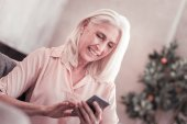 Aged cute lady messaging and smiling.