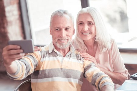 Photo pour Faisons une photo. Charmant couple joyeux sénior passer du temps ensemble souriant et faire des photos sur le smartphone . - image libre de droit