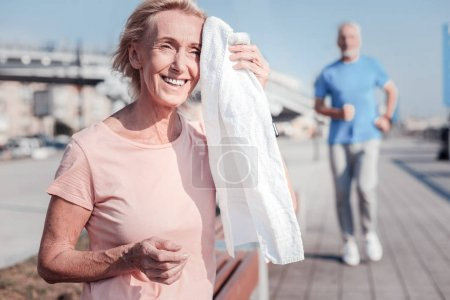 Satisfied senior woman smiling and wiping with a towel.