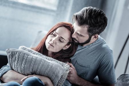 Forgive me. Redhead sad exhausted woman hugging pi...